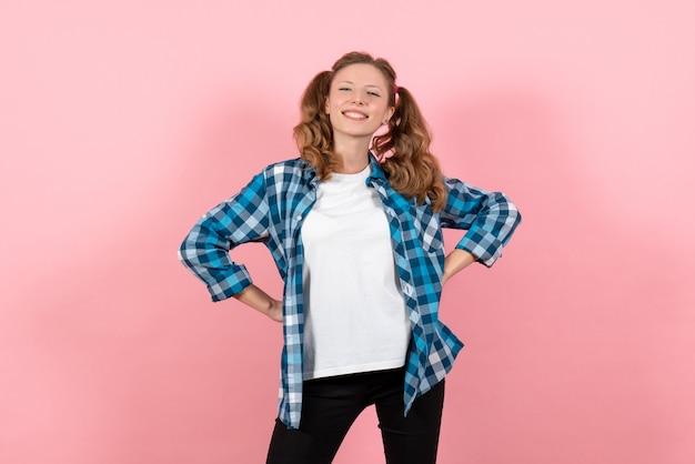 ピンクの背景の女性の感情の女の子のファッションカラーモデルでポーズをとる青い市松模様のシャツの正面図若い女性
