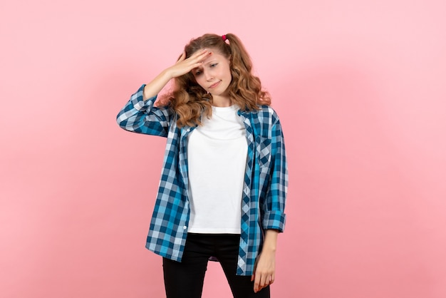 ピンクの背景にポーズをとる青い市松模様のシャツの正面図若い女性女性子供青年モデル色感情
