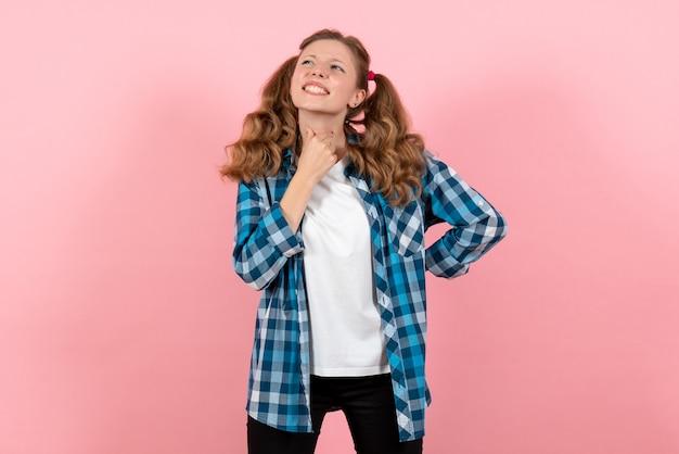明るいピンクの背景の女の子の若者の感情モデルファッションの子供にポーズをとって青い市松模様のシャツの正面図若い女性