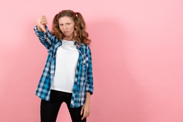 ピンクの背景にポーズをとる青い市松模様のシャツの正面図若い女性感情の女の子ファッションモデル青年