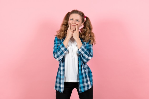 ピンクの背景の女性の感情の女の子のファッションの色モデルでポーズをとる青い市松模様のシャツの正面図若い女性