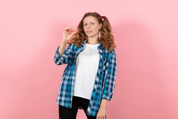 ピンクの背景にポーズをとる青い市松模様のシャツの正面図若い女性若者の感情女の子モデルファッション子供