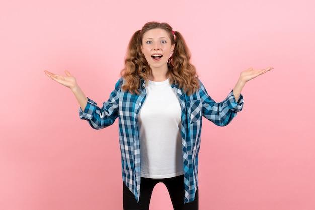 ピンクの机の若者の感情の女の子の子供モデルのファッションでポーズをとる青い市松模様のシャツの正面図若い女性