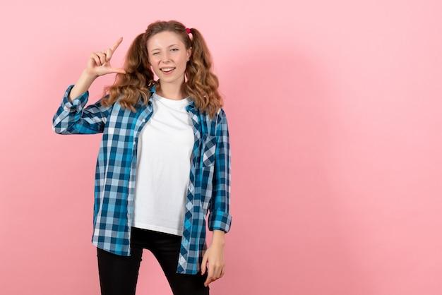 ピンクの机の若者の感情の女の子モデルの子供のファッションでポーズをとる青い市松模様のシャツの正面図若い女性