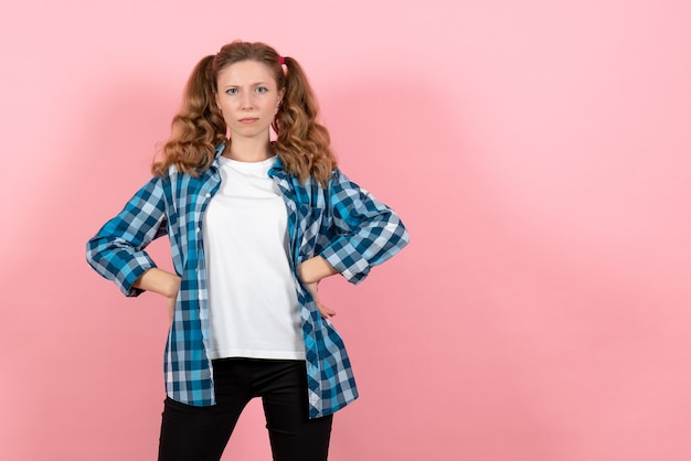 ピンクの背景にポーズをとる青い市松模様のシャツを着た若い女性の正面図若者の感情の女の子モデルの子供のファッション