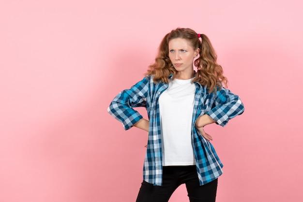 분홍색 배경에 미친 표정으로 포즈 파란색 체크 무늬 셔츠에 전면보기 젊은 여성 여자 감정 모델 패션 소녀 색상