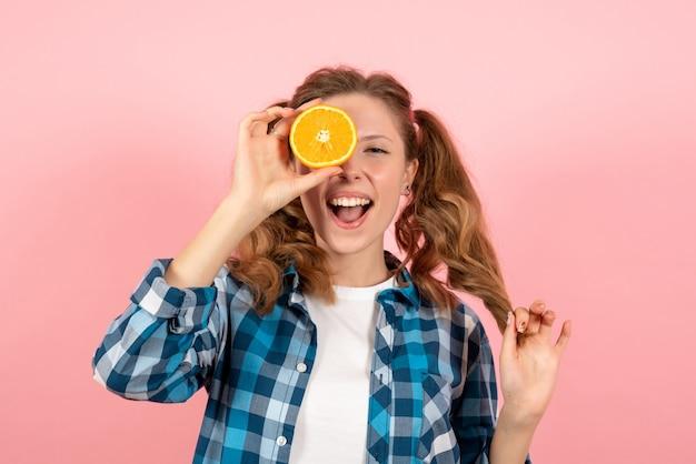 ピンクの背景の女性の人間の感情モデルファッションの女の子にオレンジ色でポーズをとって青い市松模様のシャツの正面図若い女性