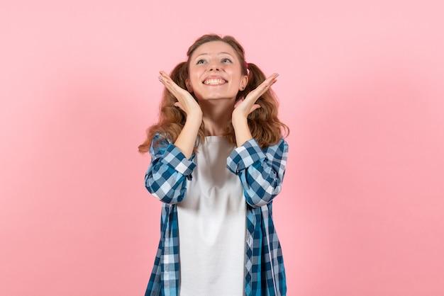분홍색 배경 여자 감정 모델 패션 여자 색상에 약간의 미소로 포즈 파란색 체크 무늬 셔츠에 전면보기 젊은 여성