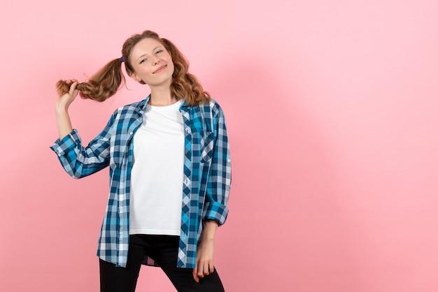 분홍색 배경 여자 감정 여자 패션 컬러 모델에 미소로 포즈를 취하는 파란색 체크 무늬 셔츠에 전면보기 젊은 여성