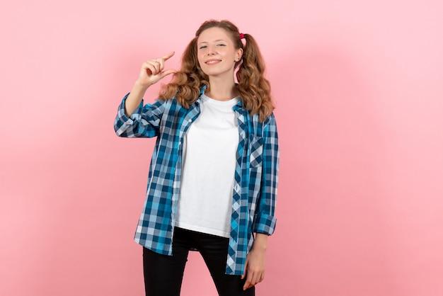 正面図ピンクの背景に笑顔でポーズをとる青い市松模様のシャツの若い女性