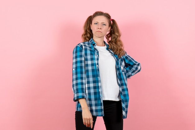 ピンクの背景に狂った表情の青い市松模様のシャツを着た若い女性の正面図