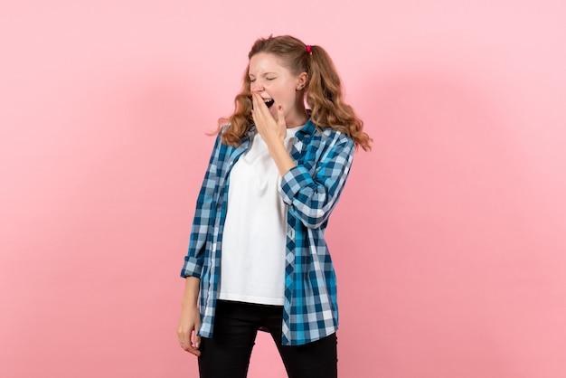 ピンクの背景の感情の女の子のファッションモデルの若者の子供であくびをしている青い市松模様のシャツの正面図若い女性