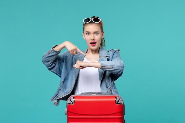 青い上着を着た若い女性の正面図青い空間で時間をチェックする旅行の準備をしています