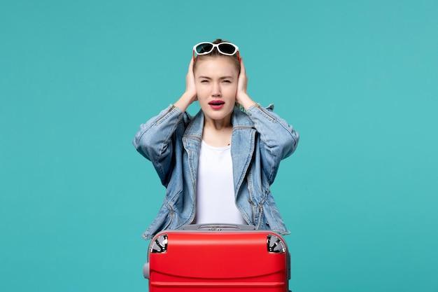 파란색 재킷에 전면보기 젊은 여성 푸른 공간에 그녀의 귀를 덮고 여행을 준비하고