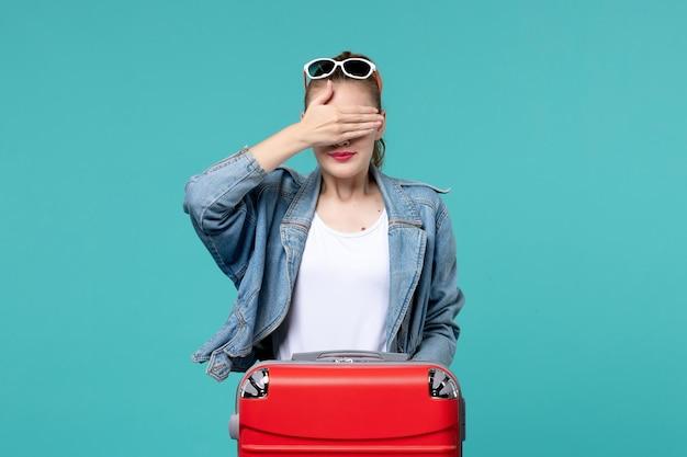 Вид спереди молодая женщина в синей куртке готовится к поездке, прикрывая глаза на синем пространстве