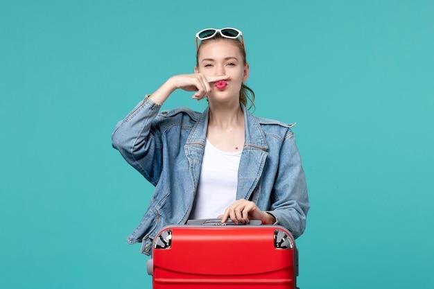 青いスペースで旅行の準備をしている青いジャケットの正面図若い女性