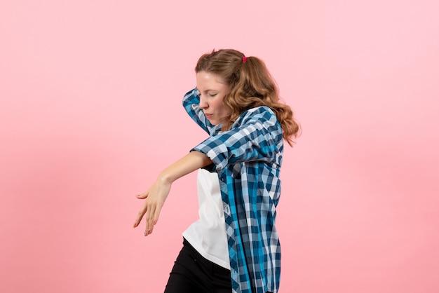 ピンクの背景で踊る市松模様のシャツを着た若い女性の正面図青年モデルの感情女性の子供の女の子