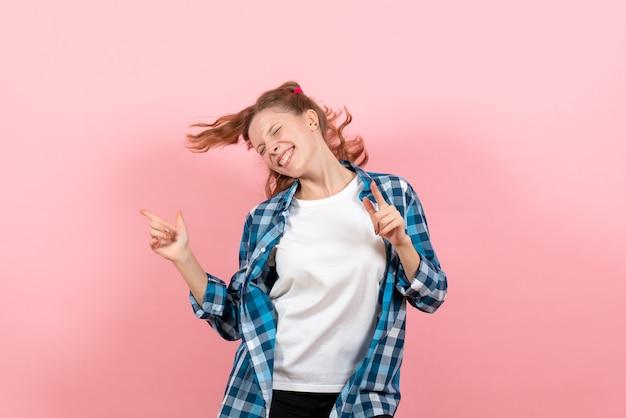 ピンクの背景にポーズをとって踊る市松模様のシャツを着た若い女性の正面図青年モデルの感情女性の子供の女の子