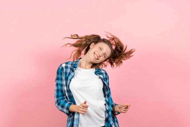正面図ピンクの背景にポーズをとって自由に感じる市松模様のシャツの若い女性青年モデルの感情女性の子供の女の子