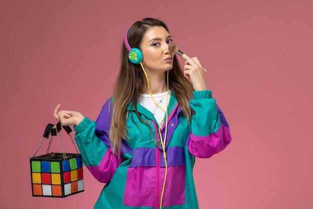 ピンクの壁にバッグを保持しているカラフルなモダンなコートのイヤホンで若い女性の正面図