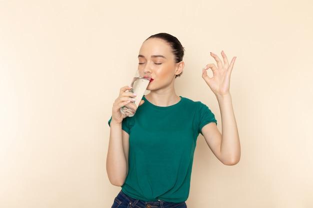 Вид спереди молодая женщина в темно-зеленой рубашке и синих джинсах, пьющая стакан воды на бежевом