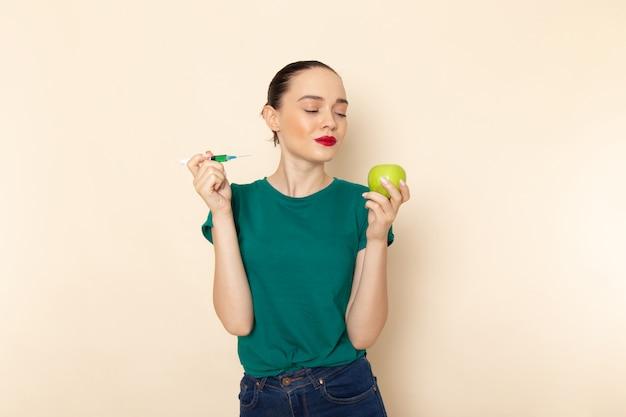 暗い緑のシャツとベージュにリンゴと注射を保持しているブルージーンズの正面の若い女性