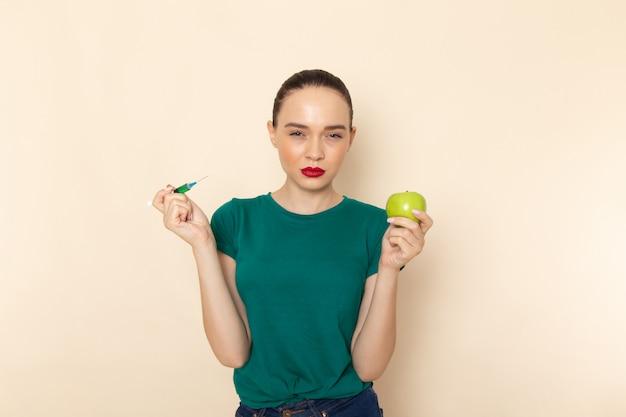 ダークグリーンのシャツとベージュにリンゴと注射を保持しているブルージーンズの正面の若い女性