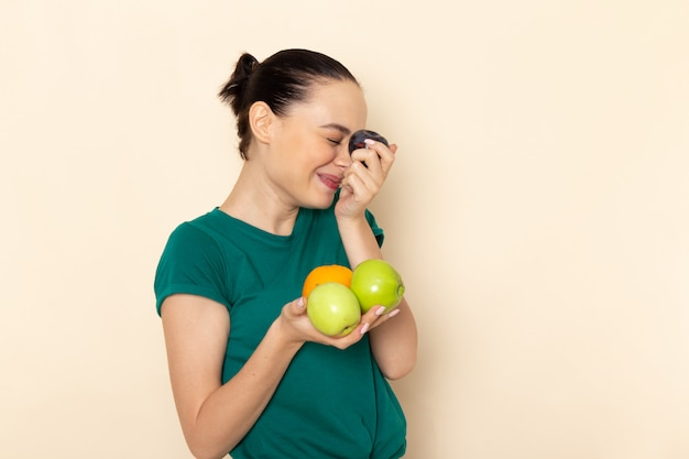 暗い緑のシャツとベージュにさまざまな果物を保持しているブルージーンズの正面の若い女性