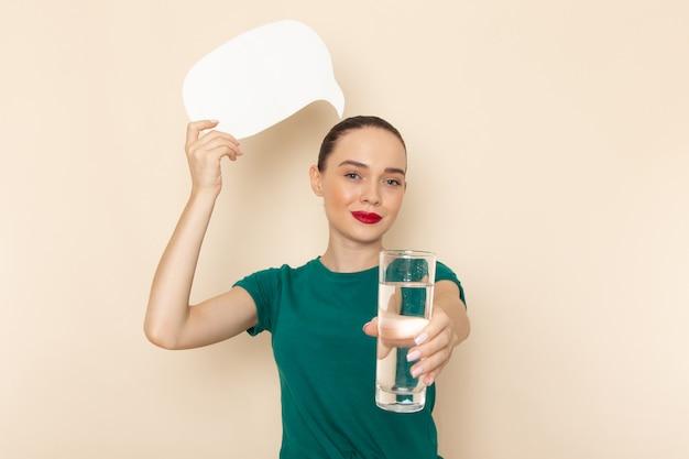 Вид спереди молодая женщина в темно-зеленой рубашке и синих джинсах, держащая стакан воды и белый знак на бежевом