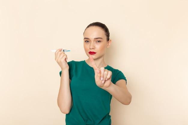 濃い緑色のシャツとブルージーンズのベージュのデスクの女性モデルの色に注射を保持している正面の若い女性