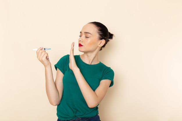 濃い緑色のシャツとブルージーンズにベージュの注射を保持している正面の若い女性