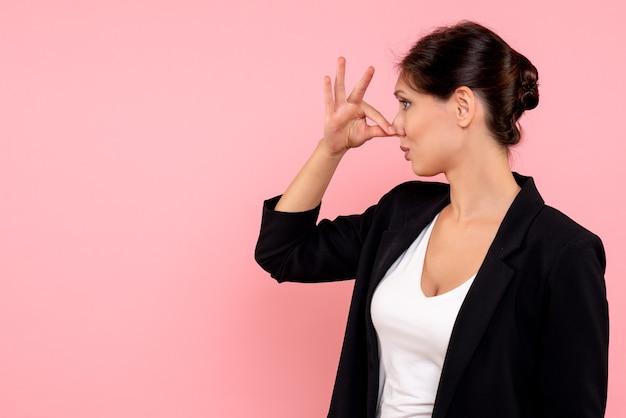 Вид спереди молодая женщина в темной куртке, закрывая нос на розовом фоне
