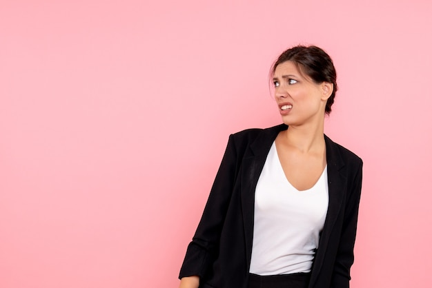 ピンクの背景に不機嫌な暗いジャケットの正面図若い女性