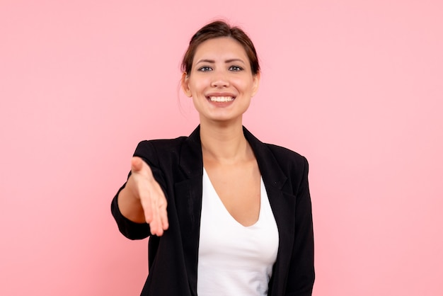 ピンクの背景に暗いジャケットの挨拶で正面図若い女性