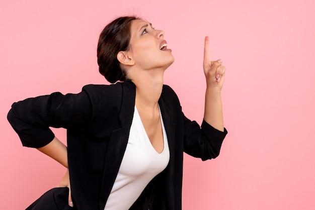 ピンクの背景に背中の痛みを持っている暗いジャケットの正面図若い女性