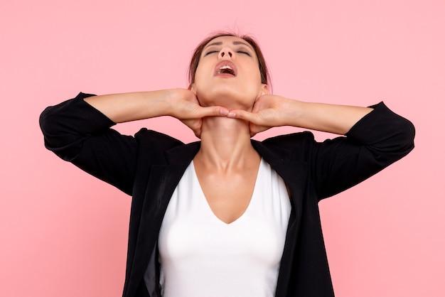 ピンクの背景に喉の痛みを持っている暗いジャケットの正面図若い女性