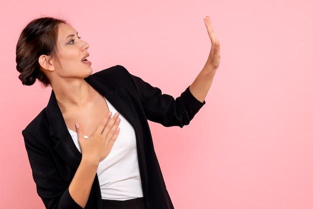 ピンクの背景に暗いジャケットの正面図若い女性