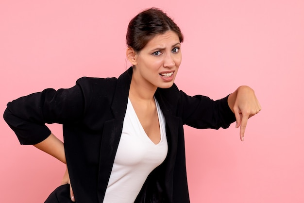 Вид спереди молодая женщина в темной куртке на розовом фоне