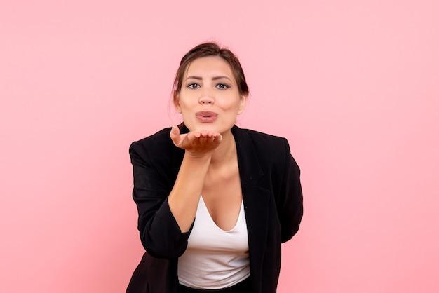 ピンクの背景に空気のキスを送信する暗いジャケットの正面図若い女性