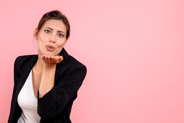 ピンクの背景にキスを送信する暗いジャケットの正面図若い女性
