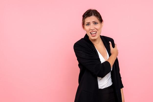 ピンクの背景に手の痛みに苦しんでいる暗いジャケットの若い女性の正面図