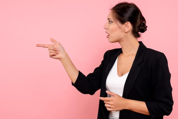 ピンクの背景で誰かと話している暗いジャケットの正面図若い女性