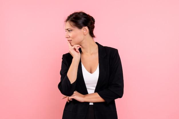 분홍색 배경에 어두운 재킷 생각에 전면보기 젊은 여성
