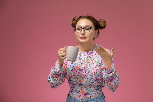 花の正面の若い女性のデザインのシャツとピンクの背景に臭いがするカップを保持しているブルージーンズ