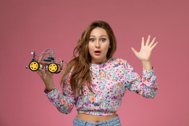 花の正面の若い女性設計されたシャツとピンクの背景におもちゃの車を保持しているブルージーンズ