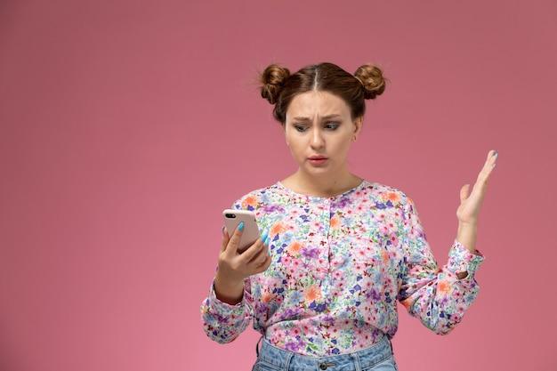 Вид спереди молодая женщина в рубашке с цветочным дизайном и синих джинсах держит и использует телефон на розовом фоне