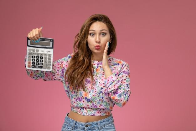 Вид спереди молодая женщина в рубашке с цветочным дизайном и синих джинсах держит калькулятор на розовом столе