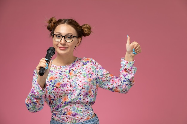 花の正面の若い女性のデザインのシャツと明るい背景で歌おうとしてマイクを保持しているブルージーンズ