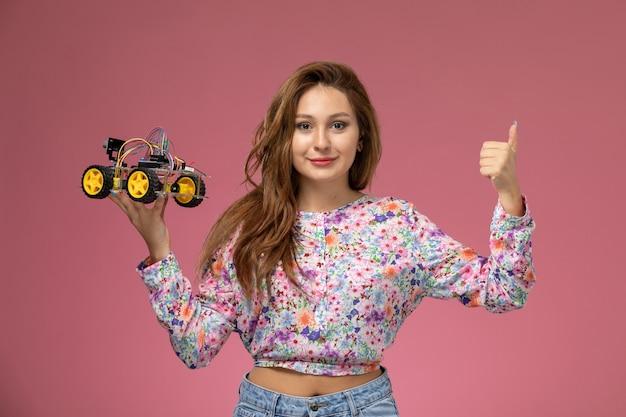 花の正面の若い女性のデザインのシャツとピンクの背景に笑みを浮かべておもちゃの車を保持しているブルージーンズ