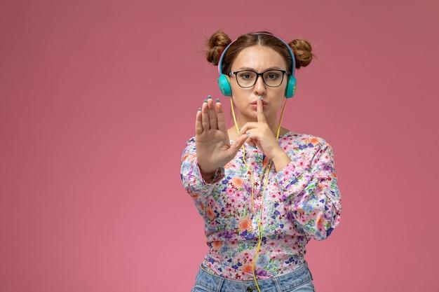 花の正面若い女性設計されたシャツとブルージーンズにピンクの背景にイヤホンで音楽を聴く